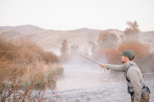 A man standing casting his fishing rod, fly fishing from a riverbank.の写真素材 [FYI02252020]