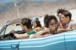 A group of friends in a pale blue convertible on the open road, driving across a dry flat plain surrの写真素材 [FYI02252022]