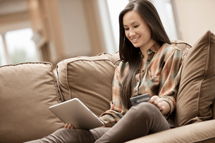 A woman sitting on a sofa at home holding a digital tablet and a credit card, shopping online.の写真素材 [FYI02252027]