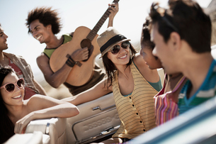A group of friends in a pale blue convertible on the open road, driving across a dry flat plain surrの写真素材 [FYI02252031]