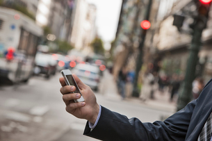 A working day. Businessman in a work suit and tie on a city street, checking his phone.の写真素材 [FYI02252033]