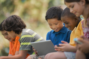 A row of children sitting outdoors in summer using tablets and handheld games.の写真素材 [FYI02252043]