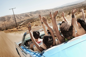 A group of friends in a pale blue convertible on the open road, driving across a dry flat plain surrの写真素材 [FYI02252052]
