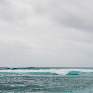 Waves breaking on a beach, turquoise water and an overcast sky.の写真素材 [FYI02252063]