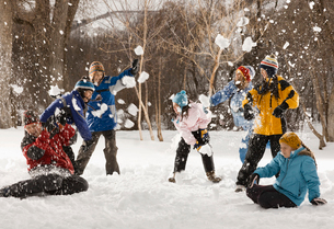 Four people outdoors in hats, coats and scarves, having an energetic snowball fight.の写真素材 [FYI02252065]