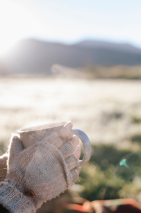 A person wearing mittens holding a hot drink in her hands.の写真素材 [FYI02252076]