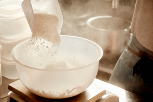 A baker preparing ingredients, using a measuring scale and pouring flour into a bowl.の写真素材 [FYI02252077]