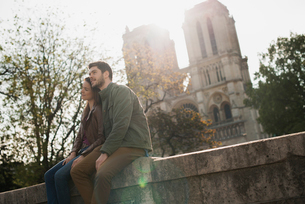 A couple in a romantic mood, side by side with arms around each other outside Notre Dame Cathedral iの写真素材 [FYI02252079]