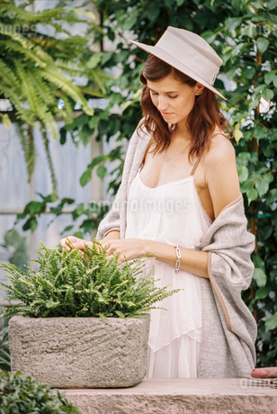 A woman in a sunhat, light clothes and shawl in a garden.の写真素材 [FYI02252084]