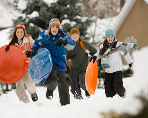 Winter snow. Four children, boys and girls, running across snow carrying sledges.の写真素材 [FYI02252086]