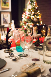 A table laid for a Christmas meal, with silver and crystal glasses and a Christmas tree in the backgの写真素材 [FYI02252089]