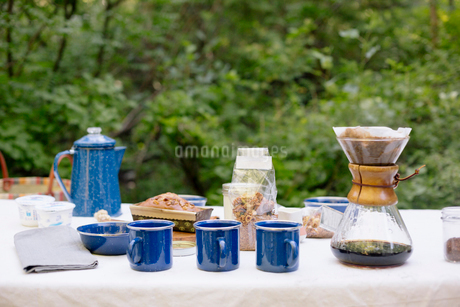 Table in a garden, with a coffee maker, mugs and bowls, a cake and cereal.の写真素材 [FYI02252095]