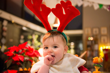 A family at home on Christmas Day. A baby girl wearing felt antlers.の写真素材 [FYI02252127]
