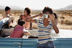 A group of friends by a pale blue convertible on the open road, on a flat plain surrounded by mountaの写真素材 [FYI02252132]
