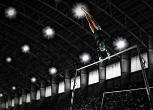 A gymnast, a young woman performing a routine on the parallel bars.の写真素材 [FYI02252134]