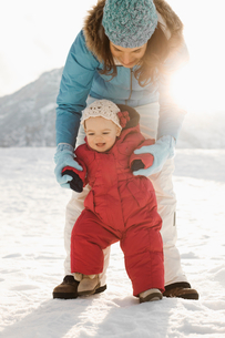 A mother and baby outdoors in the snow, a baby upright learning to walk.の写真素材 [FYI02252149]