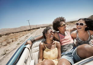 Three young people in a pale blue convertible car, driving on the open road across a flat dry plain,の写真素材 [FYI02252152]