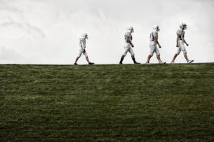 A group of four football players in sports uniform, three tall figures and one shorter team player lの写真素材 [FYI02252174]