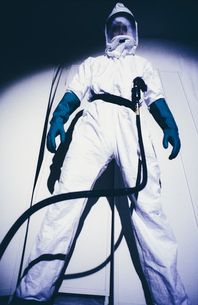 A man in a protective suit and a mask, standing with legs apart looking down, a breathing hose clippの写真素材 [FYI02252175]