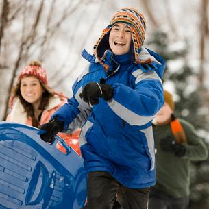 Winter snow. Three children running, carrying sledges.の写真素材 [FYI02252181]