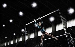 A gymnast, a young woman performing a routine on the parallel bars.の写真素材 [FYI02252186]