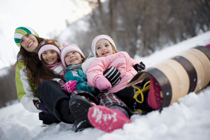 three children and an adult woman seated on a sledge in the snow.の写真素材 [FYI02252190]