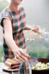 A woman holding two glasses and reaching for a bottle of wine.の写真素材 [FYI02252213]
