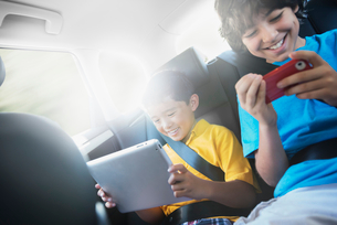 Two children travelling in the back seat of a car, one using a digital tablet and one a handheld gamの写真素材 [FYI02252216]