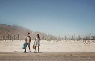 A young couple carrying suitcases, standing by the roadside,  by a wind farm in open country.の写真素材 [FYI02252217]
