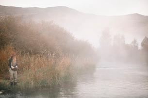 A woman fishing, standing on the riverbank. Mist rising from the water.の写真素材 [FYI02252231]
