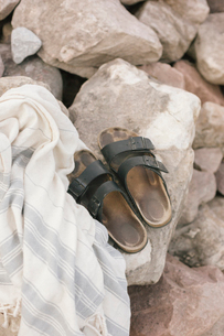 A shawl and pair of sandals on a rock.の写真素材 [FYI02252235]