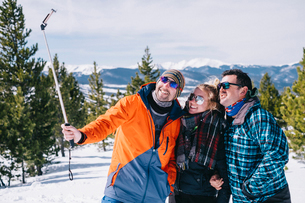 Three people, two men and a young woman in skiing gear posing for a selfie, one holding a selfie stiの写真素材 [FYI02252241]