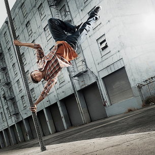 A young man breakdancing, leaping in the air, and stretching out.の写真素材 [FYI02252244]