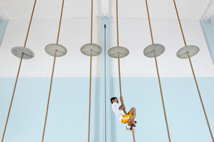 A boy climbing up a rope at the gym.の写真素材 [FYI02252245]