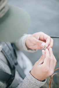 A person's hands tying a fishing fly onto a hook.の写真素材 [FYI02252247]