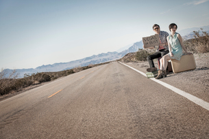 A young couple, man and woman, on a tarmac road in the desert hitchiking, with a sign saying Vegas oの写真素材 [FYI02252254]