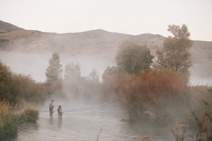 A couple, a man and woman standing in mid stream fly fishing in a river.の写真素材 [FYI02252257]
