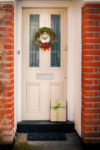 Christmas decorations. A Christmas wreath with a red bow on the front door of a house.の写真素材 [FYI02252259]