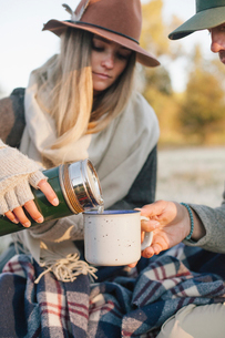 A woman pouring a hot drink from a vacuum flask into a cup on a winter picnic.の写真素材 [FYI02252267]
