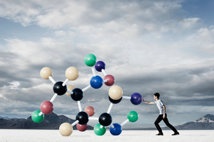 A teenage boy putting his hand out to push a large molecular structural model away from him.の写真素材 [FYI02252275]