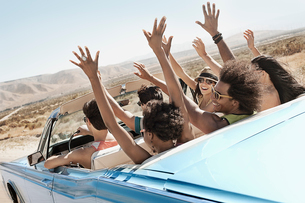 A group of friends in a pale blue convertible on the open road, driving across a dry flat plain surrの写真素材 [FYI02252280]