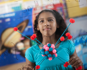 A girl holding a molecular structure and looking at a board of equations and formulae in the classroの写真素材 [FYI02252282]