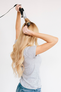 A young woman with long blond wavy hair using curling tongs. Side view.の写真素材 [FYI02252284]