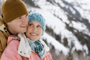 A couple hugging each other, man and woman, in the snowy mountains.の写真素材 [FYI02252294]