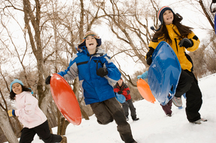 A group of children, boys and girls, running across the snow carrying sledges.の写真素材 [FYI02252300]