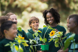 Children in a group learning about plants and flowers, carrying plants and sunflowers.の写真素材 [FYI02252303]