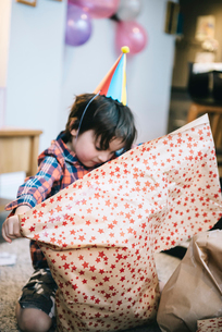 A boy unwrapping presents at a birthday party.の写真素材 [FYI02252322]