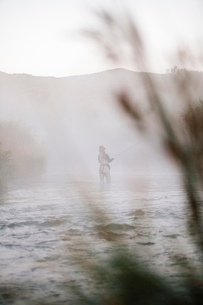 A woman fisherman fly fishing, standing in waders in thigh deep water.の写真素材 [FYI02252342]