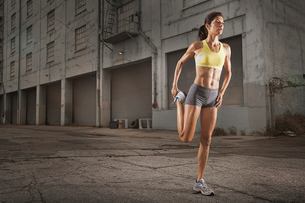 A woman in running gear, crop top and shorts, stretching her body and preparing for a run, or coolinの写真素材 [FYI02252351]