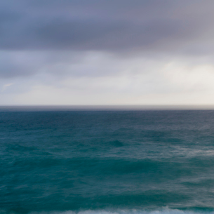 Turquoise ocean surface under a grey stormy sky.の写真素材 [FYI02252352]